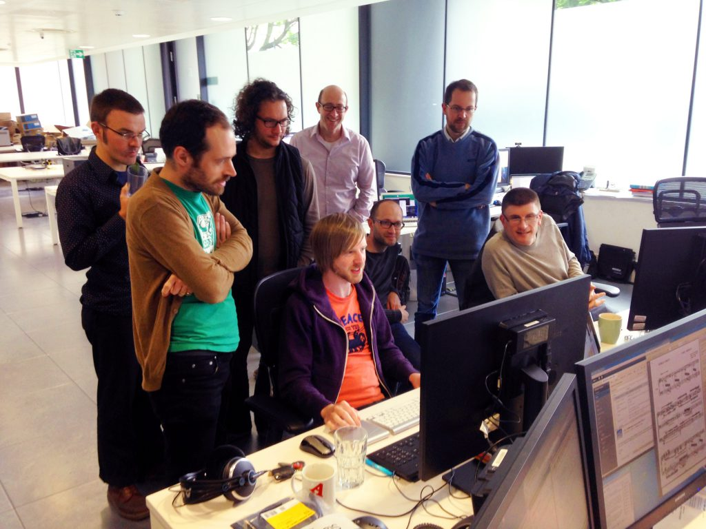 The team gathers round to watch the first edit be made.